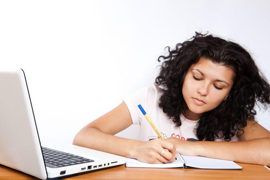 Étudiante écrivant sur un carnet en face d'un ordinateur